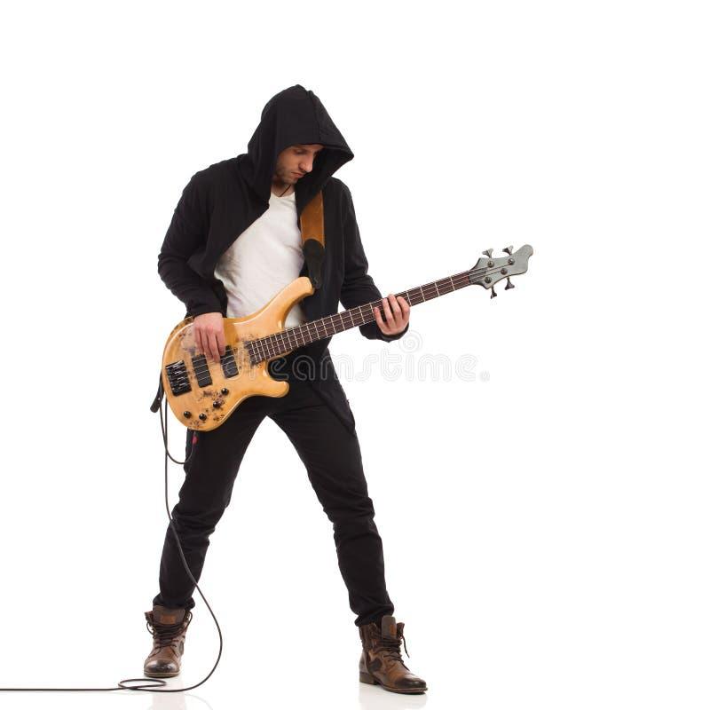O guitarrista masculino joga o baixo giutar. imagem de stock royalty free