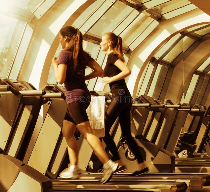O Gym disparou - em duas jovens mulheres que correm em máquinas, escada rolante fotos de stock royalty free