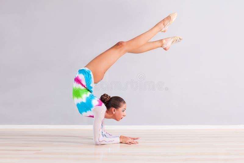 O gymnast da menina executa exercícios imagem de stock
