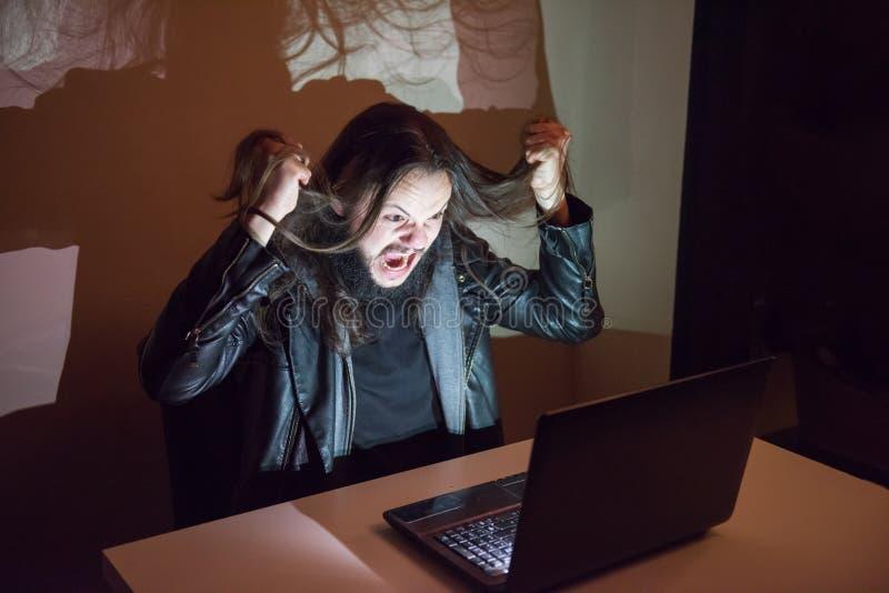 O hacker em seu computador está indo louco, puxando seu cabelo, porque obteve o cought fotografia de stock royalty free