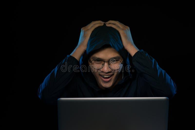 O hacker masculino bem sucedido levanta na frente do laptop, aperta os punhos, vestidos na roupa preta, exulta dados maus de term fotografia de stock