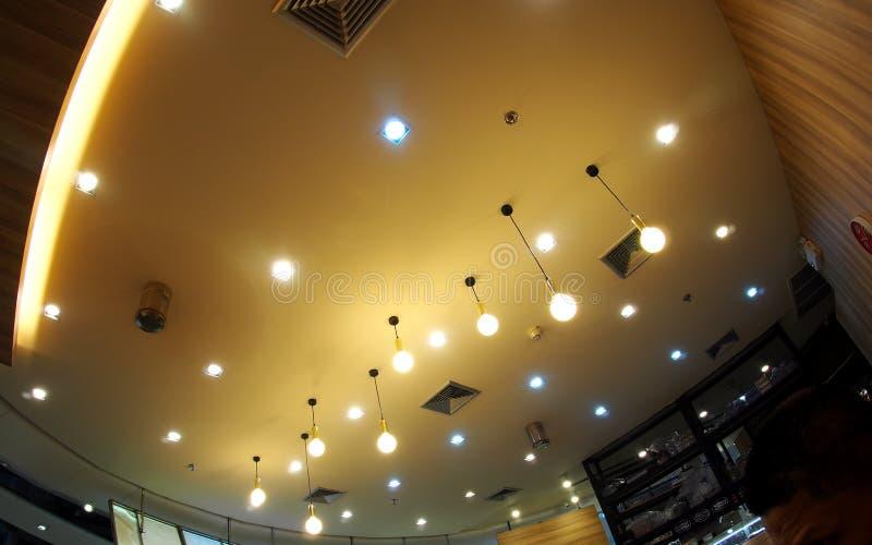 O halogênio e as lâmpadas do teto dos bulbos do diodo emissor de luz que leve com cor morna macia tonificam imagem de stock
