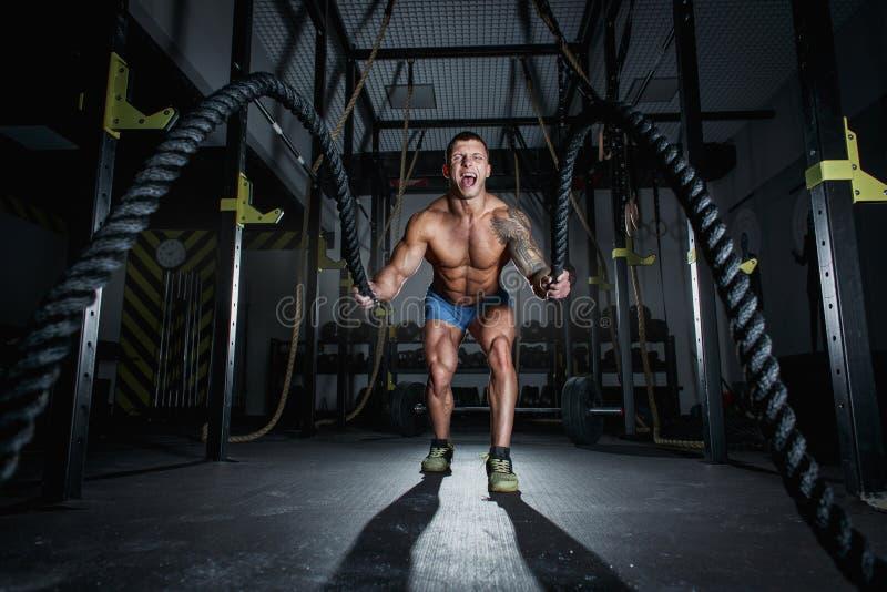 O halterofilista atlético do homem bombeado é contratado com cordas no salão do crossfit fotos de stock royalty free