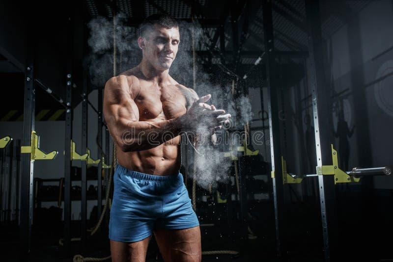 O halterofilista atlético do homem bombeado golpeia a magnésia no gym fotos de stock