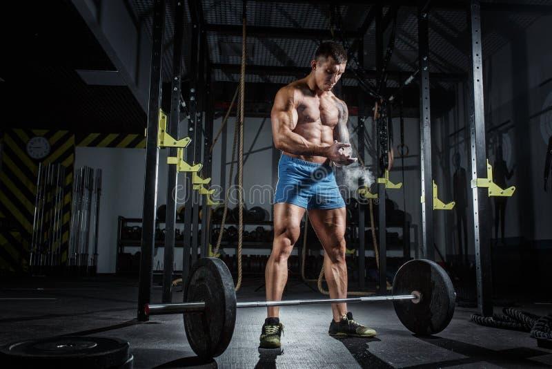 O halterofilista bombeado atlético do homem está na frente da barra no gym foto de stock
