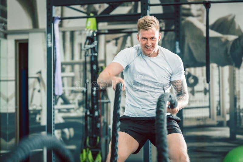 O halterofilista considerável que exercita com batalha ropes durante o treinamento funcional foto de stock