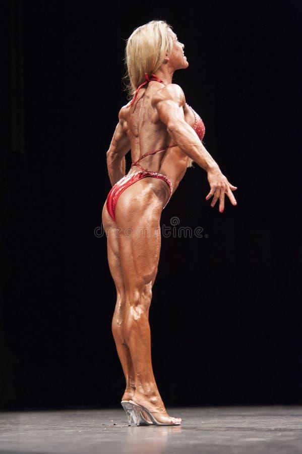 O halterofilista fêmea mostra a het a melhor pose traseira na fase foto de stock