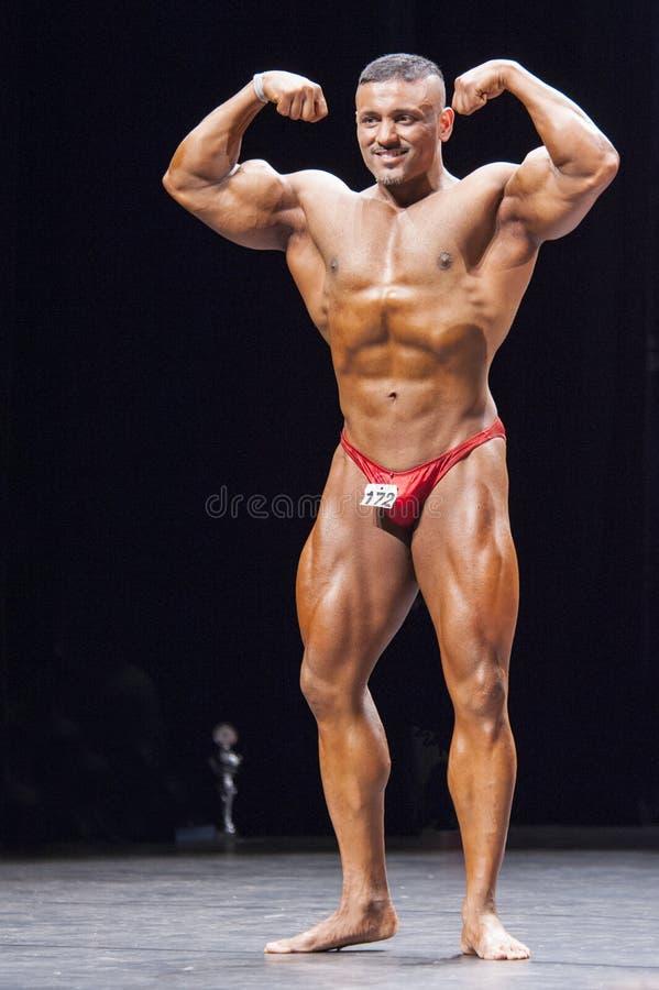 O halterofilista mostra sua pose dobro dianteira do bíceps na fase fotografia de stock