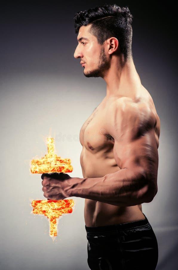 O halterofilista rasgado muscular com pesos ardentes imagem de stock royalty free