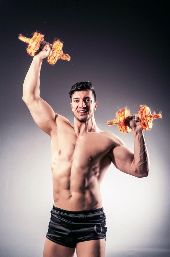 O halterofilista rasgado muscular com pesos ardentes fotografia de stock royalty free