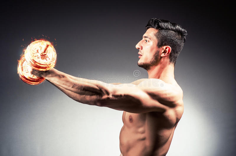O halterofilista rasgado muscular com pesos ardentes fotos de stock royalty free