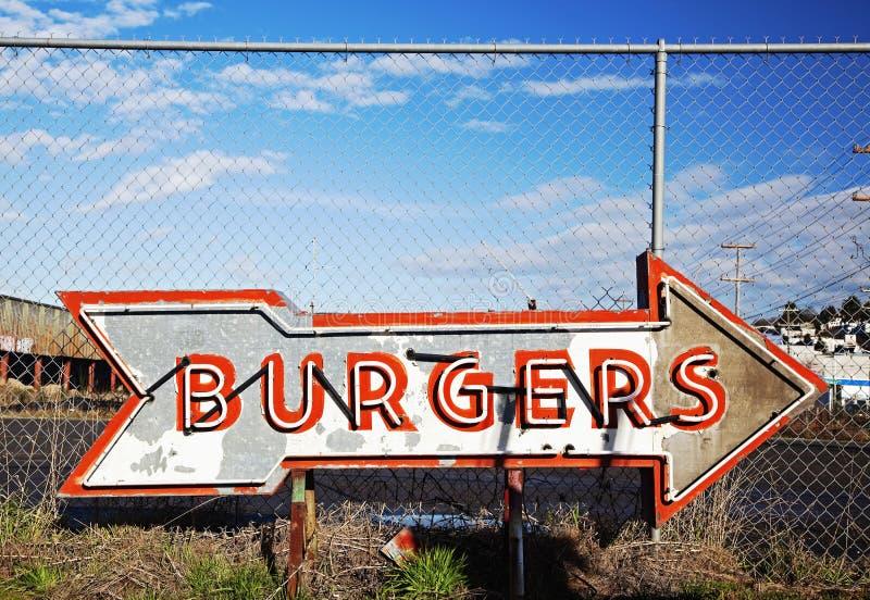 O hamburguer de néon assina dentro o scrapyard do sinal imagem de stock