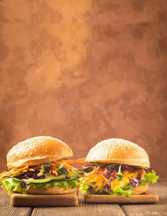 O hamburguer do vegetariano fez dos legumes frescos e dos verdes contra um fundo rústico marrom escuro Quadro vertical Copie o es fotos de stock royalty free