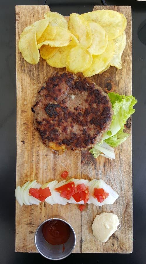 o hamburguer grelhado fresco serviu em uma bandeja de madeira imagens de stock