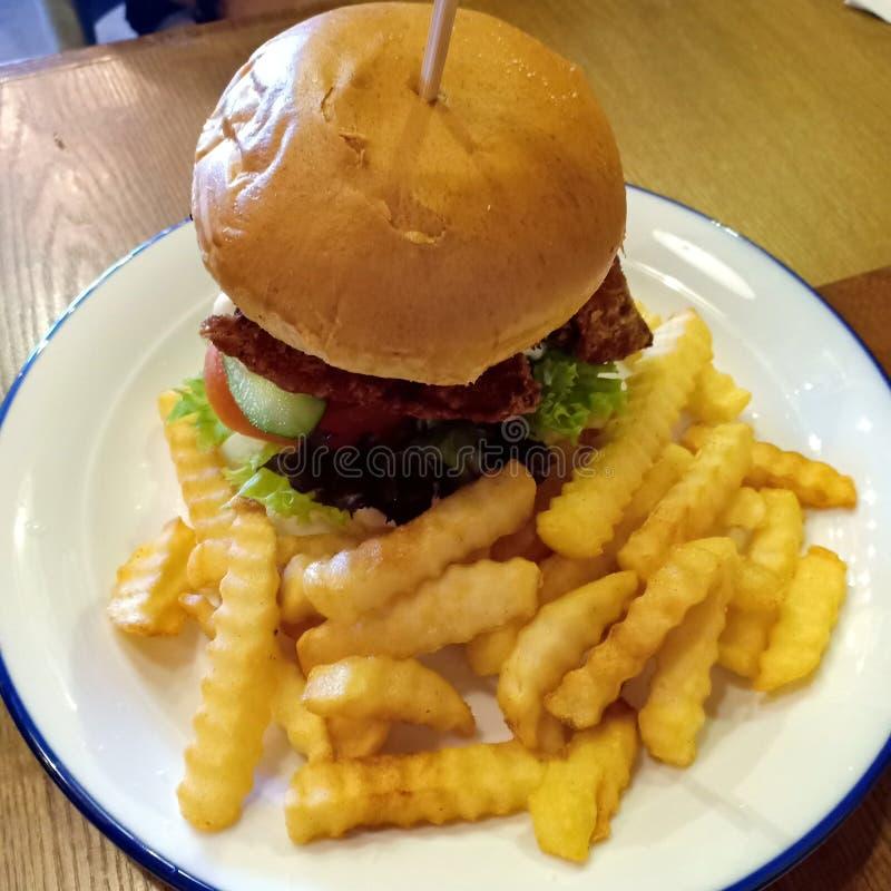 O hamburguer Meaty vem com fritadas imagem de stock