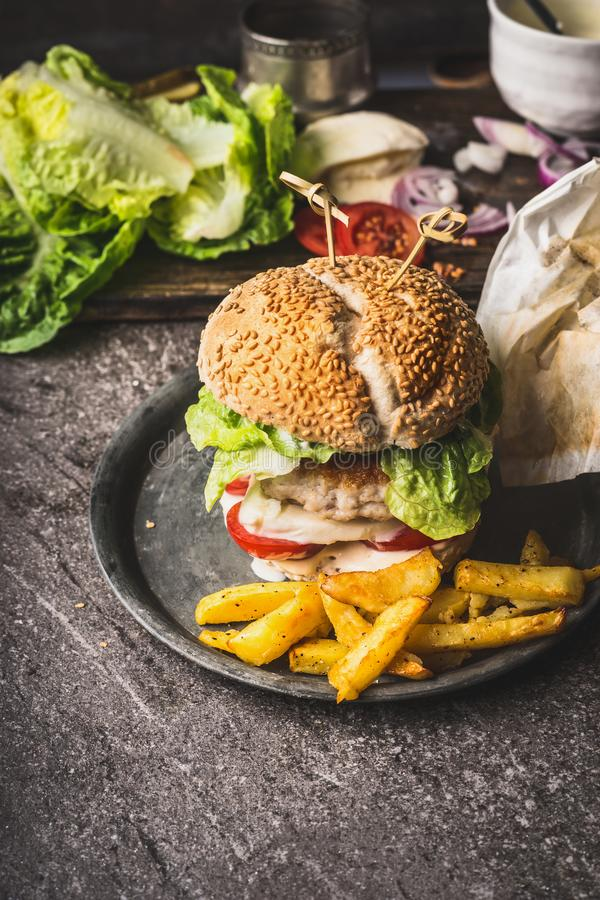 O hamburguer saboroso caseiro com galinha, alface, mussarela e tomates serviu com as batatas de batatas fritas no CCB rústico da  imagem de stock royalty free