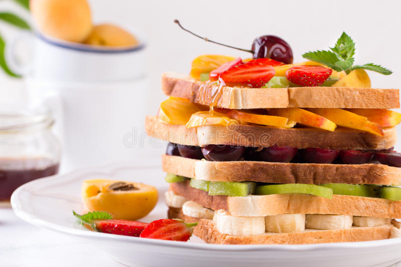 O hamburguer saudável criativo encheu-se com os frutos tropicais, as morangos e a cereja frescos cortados Conceito saudável comer imagens de stock