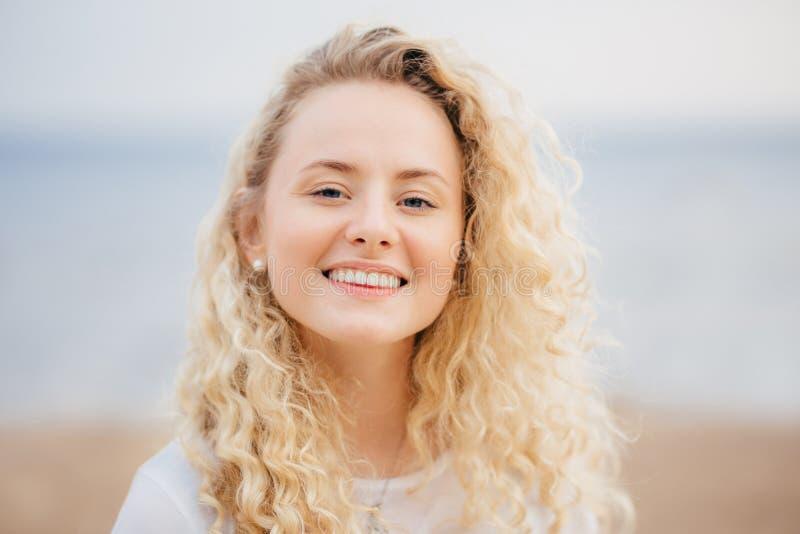 O Headshot da mulher bonita com sorriso amigável, tem a pele saudável, sendo no bom humor após o resto inesquecível no país w do  imagem de stock royalty free