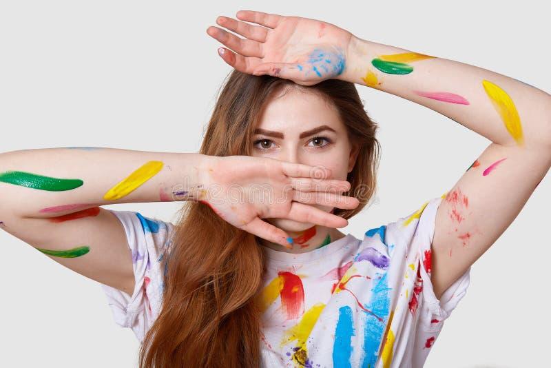 O Headshot da mulher bonito séria atrativa tem os olhos escuros, cobre a cara com as mãos, manchadas com as pinturas acrílicas co foto de stock