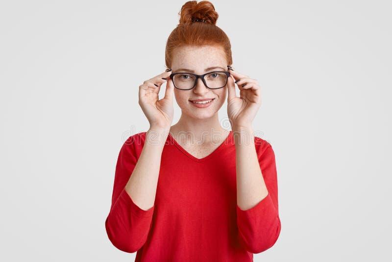 O Headshot da mulher europeia nova freckled bonita no eyewear, tem o sorriso delicado, vestido na camiseta vermelha, exulta a pro fotografia de stock royalty free