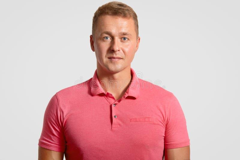 O Headshot do homem considerável atrativo tem olhar atraente, vestido na camisa ocasional do rosa t, ooks seriamente na câmera, s foto de stock