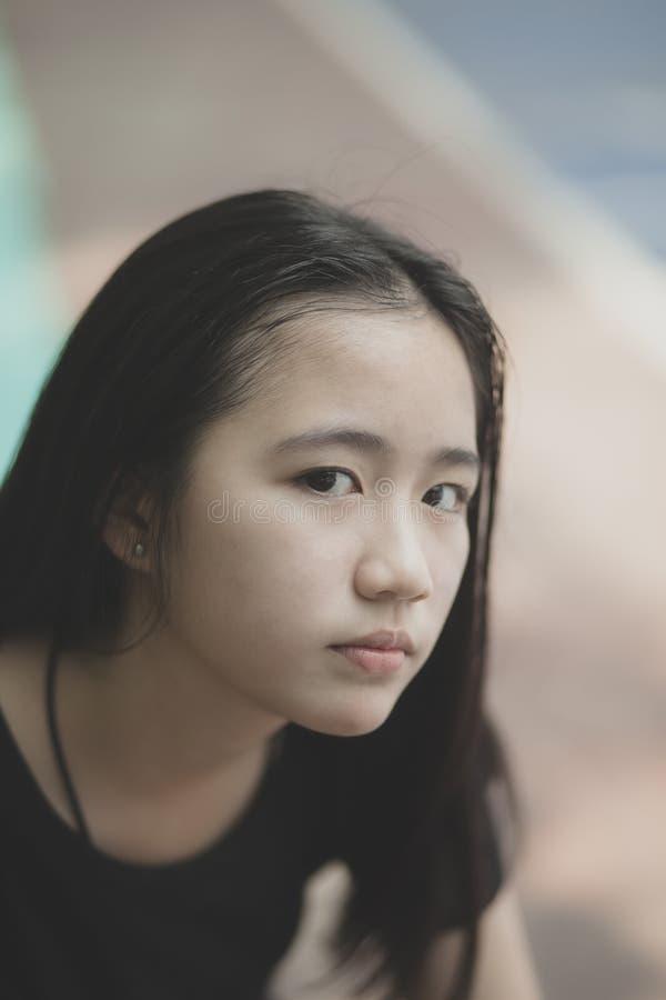 O headshot do retrato do adolescente asi?tico bonito que olha com olhos contacta exterior foto de stock