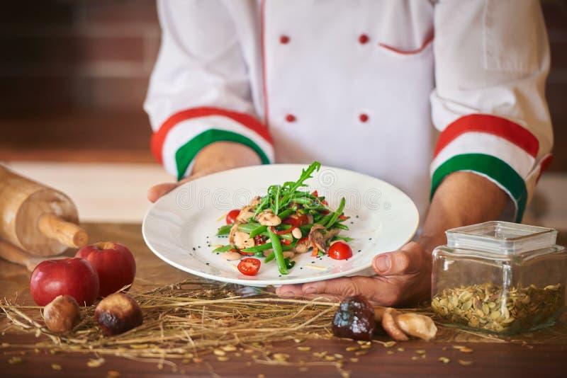 O hef do ¡ de Ð do restaurante italiano serve a salada do vegetariano imagens de stock