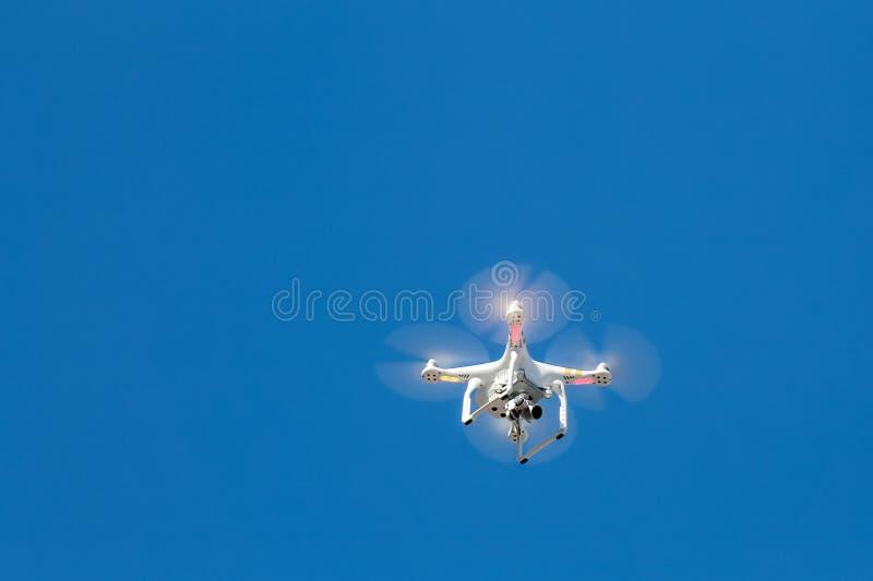 O helicóptero branco voa contra o céu, o zangão que a câmera dispara no vídeo do evento, fundo do céu azul imagem de stock royalty free