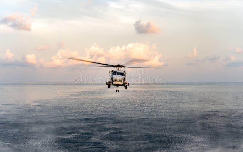 O helicóptero de Sikorsky MH-60S Seahawk da marinha tailandesa real voa ou lúpulos sobre a superfície do mar durante a busca e o  fotografia de stock