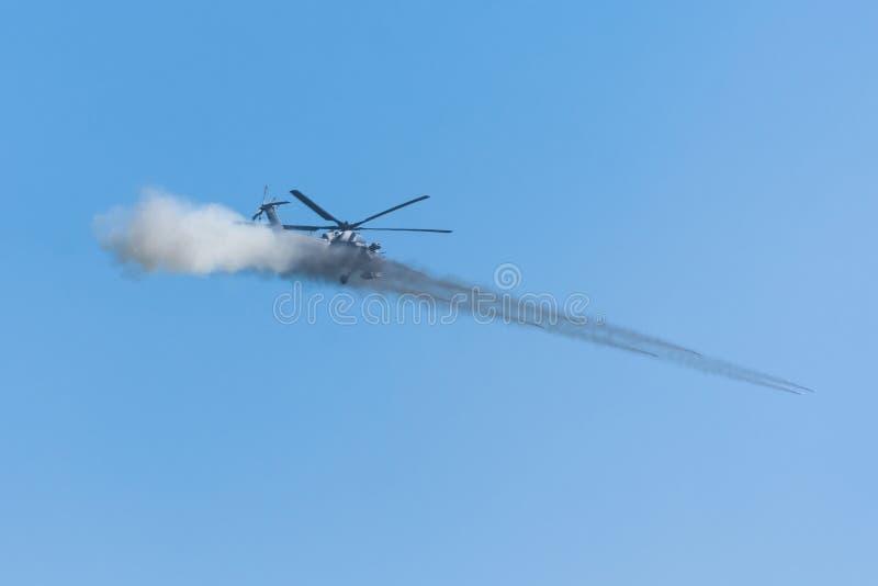 O helicóptero militar faz um tiro com uma salva de diversos mísseis com fumo imagens de stock royalty free
