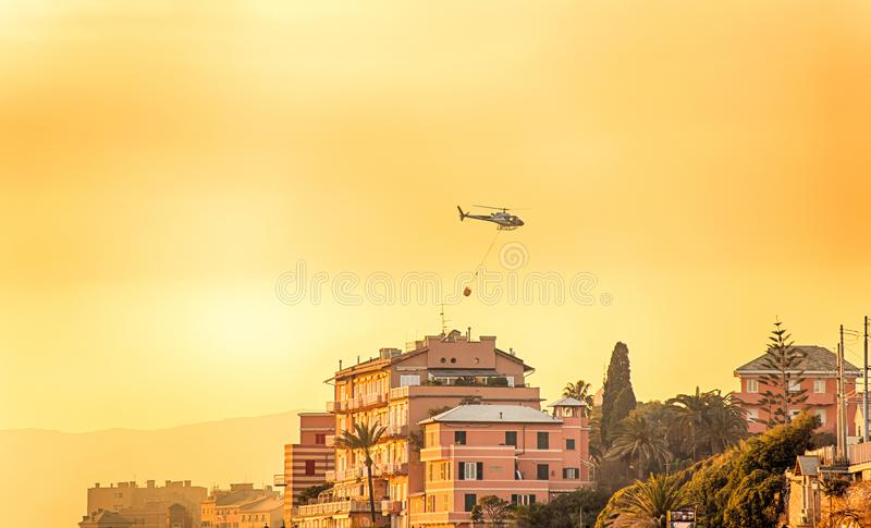O helicóptero voa sobre as casas durante um fogo no por do sol foto de stock royalty free