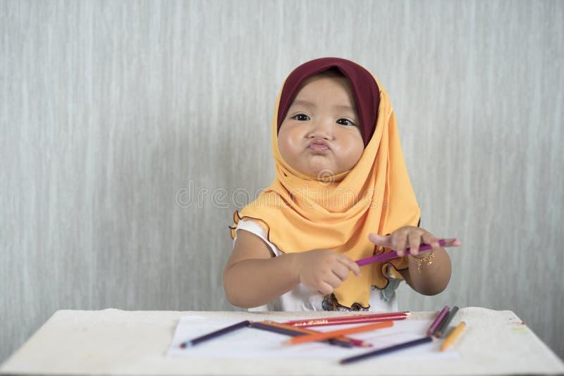 O hijab vestindo asiático da criança/bebê está tendo o divertimento que aprende usar lápis ao fazer a cara engraçada foto de stock