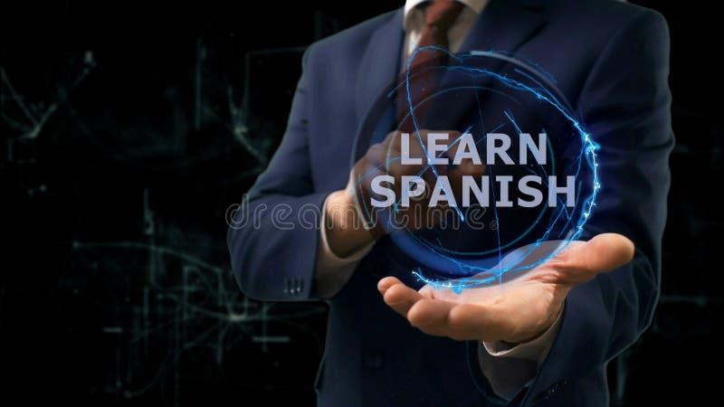 O holograma do conceito das mostras do homem de negócios aprende o espanhol em sua mão fotografia de stock