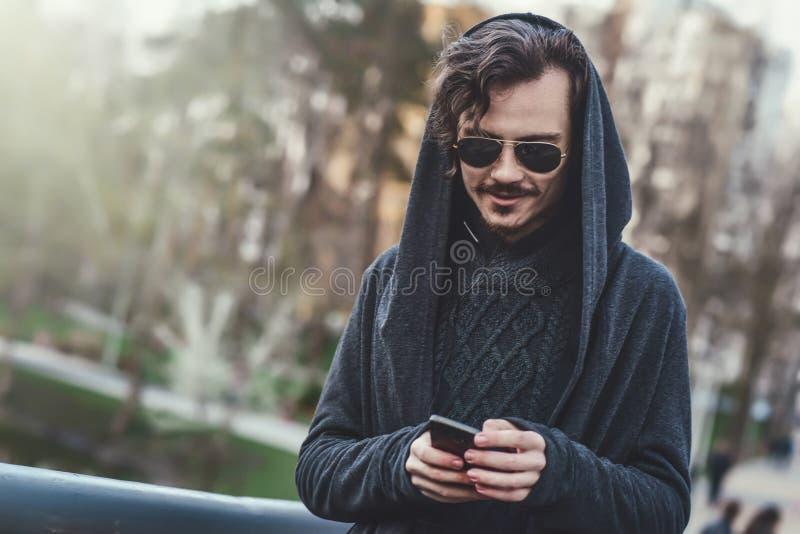 O homem ? moda encapu?ado nos ?culos de sol anda no parque e na mensagem texting imagens de stock