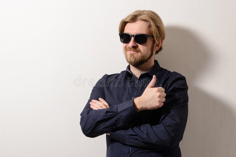 O homem à moda nos óculos de sol pretos que estão com seus braços cruzou-se em uma parede branca fotos de stock royalty free