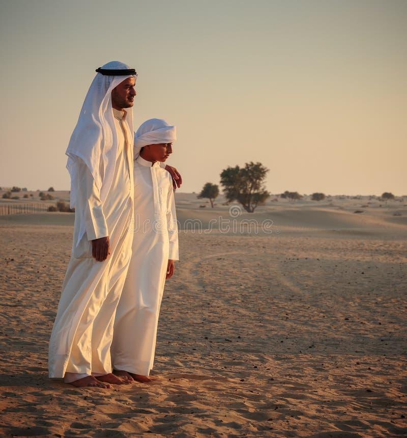 O homem árabe e um adolescente no deserto e olham o por do sol fotos de stock royalty free