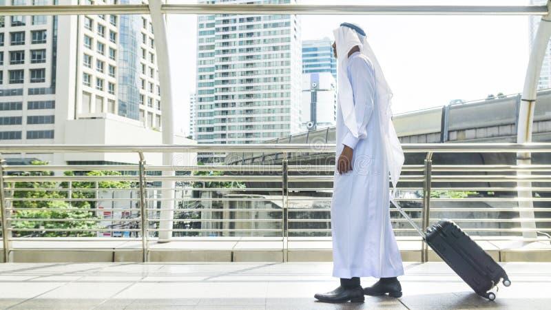 O homem árabe leva uma mala de viagem na cidade do negócio fotografia de stock