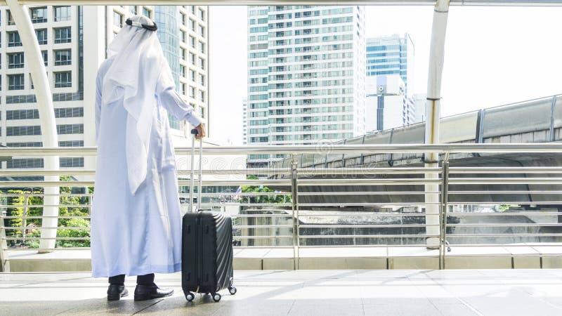 O homem árabe leva uma mala de viagem na cidade do negócio foto de stock royalty free