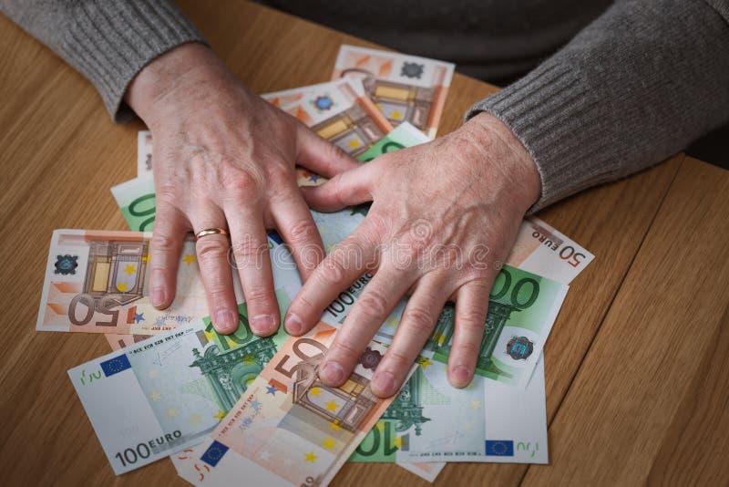 O homem ávido fecha cédulas do Euro das mãos foto de stock