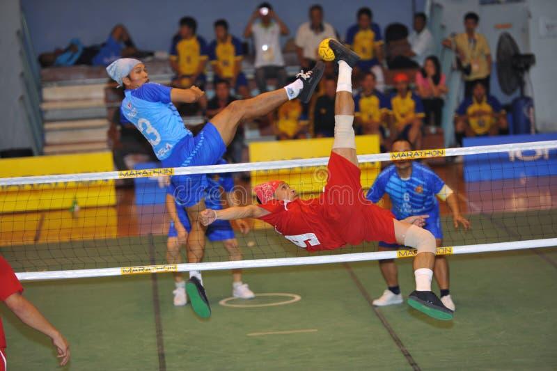 O homem é alto obstruindo a bola na rede no jogo do voleibol do pontapé, takraw do sepak fotos de stock royalty free