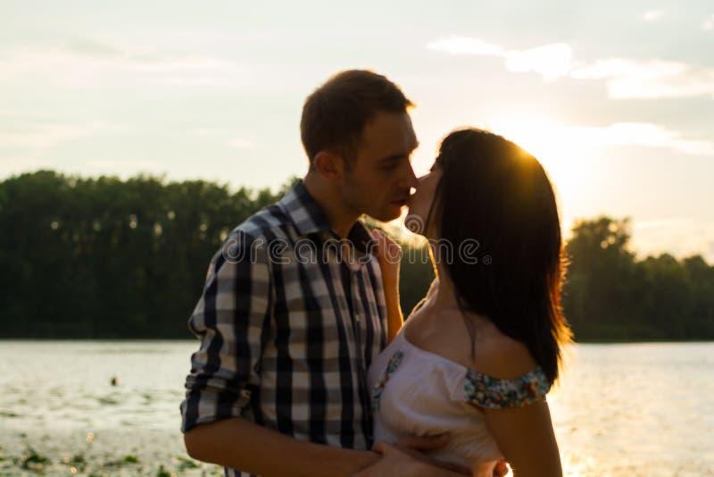 O homem é beijos a jovem mulher e abraça-a no backgro do por do sol fotos de stock royalty free