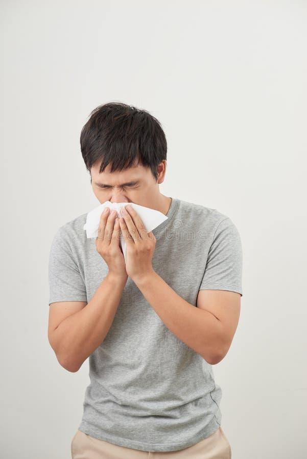 O homem é doente e espirrando com fundo branco, asiático imagem de stock
