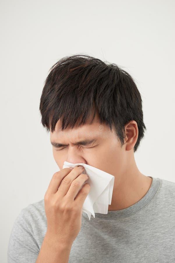 O homem é doente e espirrando com fundo branco, asiático imagens de stock royalty free