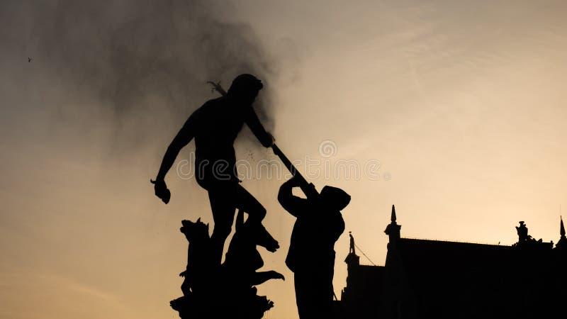 O homem é fightining/que limpa uma estátua de Netuno fotografia de stock