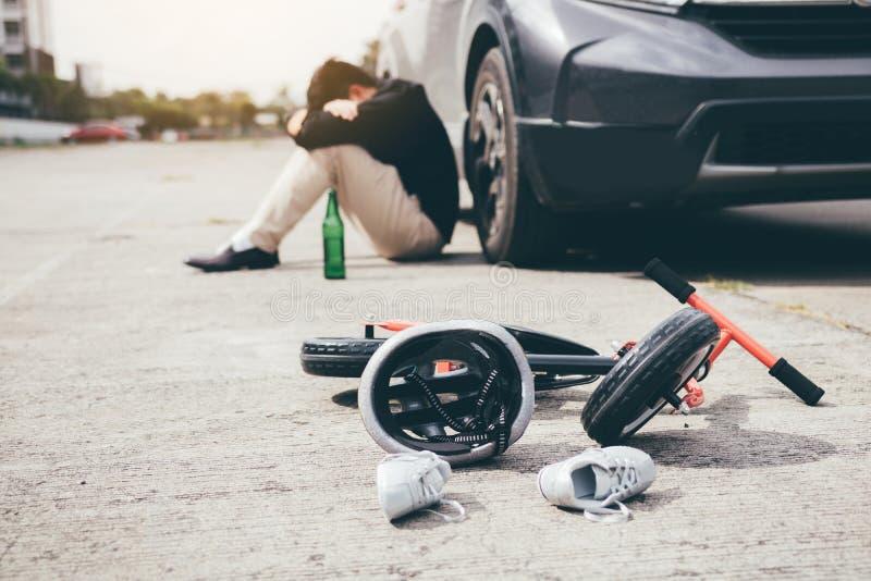 O homem é forçado ao ser bebido com condução do impacto que um acidente da bicicleta da criança ocorre foto de stock