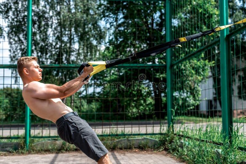 O homem é um atleta, treina a natureza a cidade, treinamento do trx do verão, motivação do equilíbrio, pele bronzeada no short Ex fotografia de stock royalty free