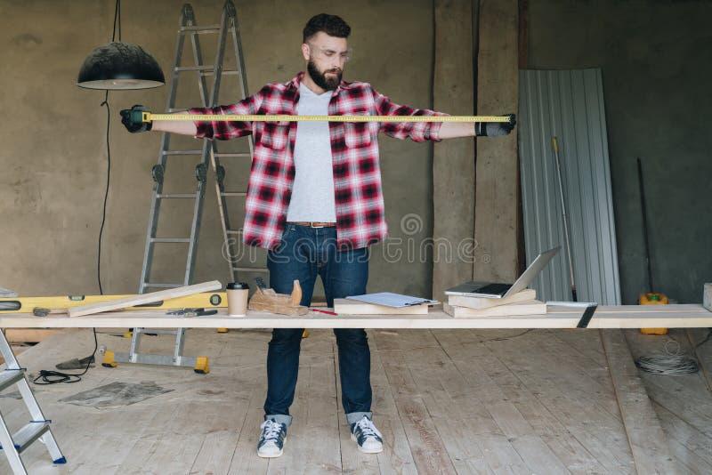 O homem é um carpinteiro, um construtor, suportes de um desenhista no trabalho imagens de stock