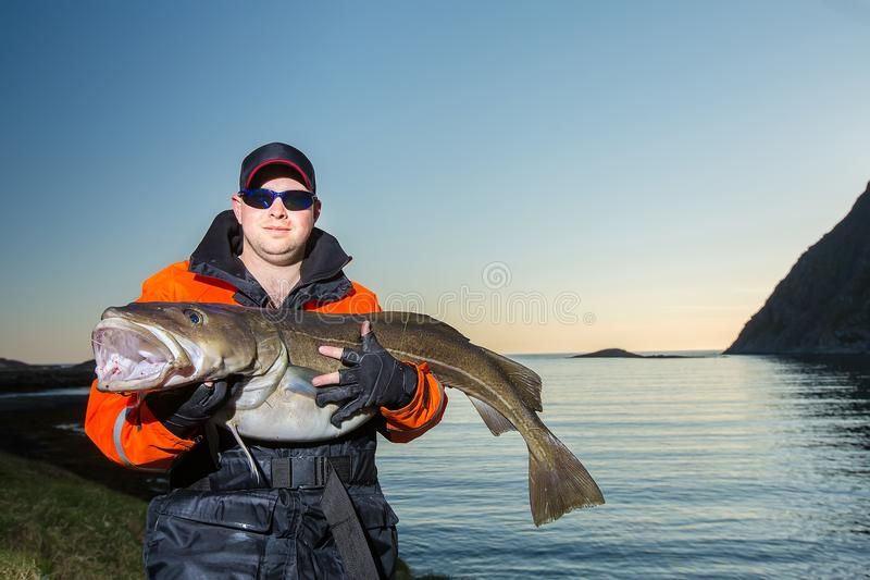 O homem é um pescador Guarda um peixe enorme em suas mãos noite foto de stock