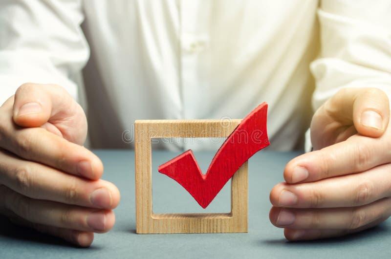 O homem abraça e protege o voto vermelho do tiquetaque O conceito da proteção contra a fraude e para apoiar a legalidade foto de stock royalty free