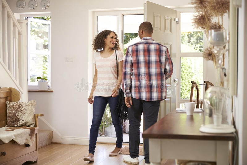 O homem abre a casa de Front Door For Woman Returning do trabalho foto de stock